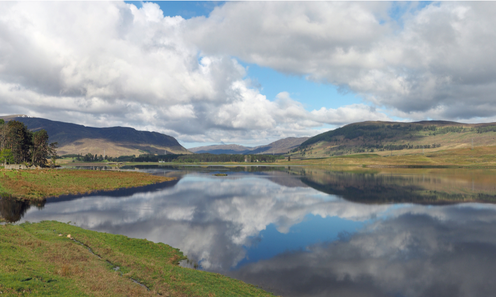 Spey river west of the dam with hills and clouds reflections, Scotland in spring